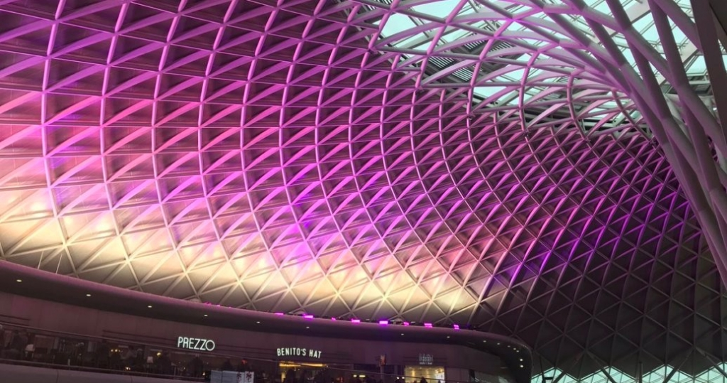 Roof of Kings Cross station lit up purple